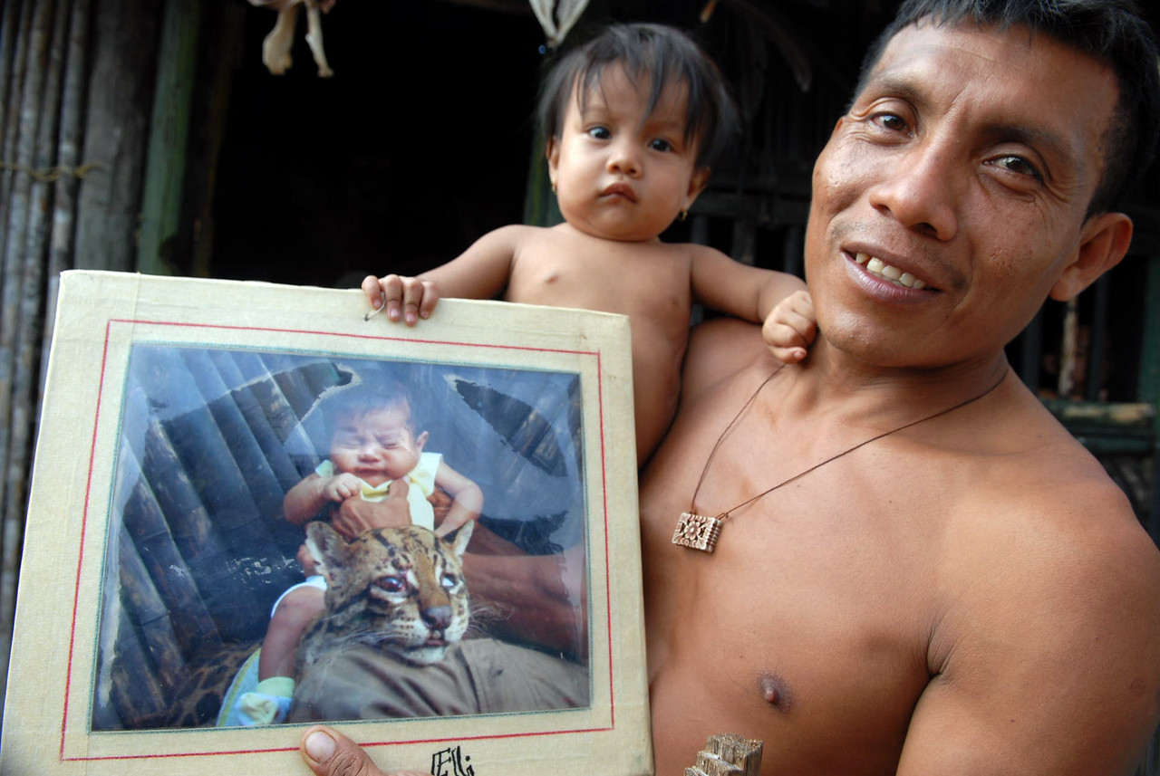 A Kuna hunter proudly shows a photo of an ocelot he shot